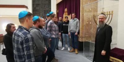 Junge Menschen und ein Rabbi stehen in einer Synagoge.
