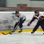 Zwei Eishockeyspielerinnen kämpfen um einen Puck.