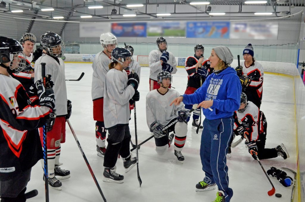 Eishockeyspieler stehen im Kreis um die Trainerin.