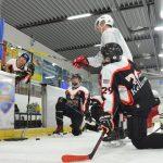 Eishockeyspieler kniene im Halbkreis auf dem Eis vor einer Tafel mit einer Zeichnung des Spielfeldes.