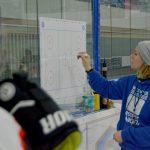 Eine Frau im blauen Kapuzenpullover zeichnet mit einem Stift auf einem Plan des Eishockey-Spielfeldes