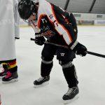 Ein Eishockeyspieler stützt sich auf seine Knie, um Luft zu holen.