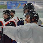 Ein Eishockeyspieler zeigt mit der Hand in eine Richtung, drei andere schauen hinterher.