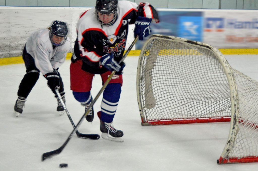 Eine Eishockeyspielerin und ein Eishockeyspieler kämpfen um einen Puck.