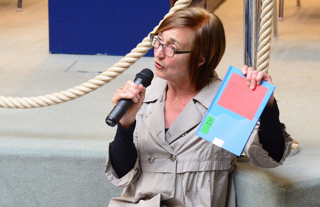 Eine Frau mit einem Mikrofon, die ein Buch in die Höhe hält.