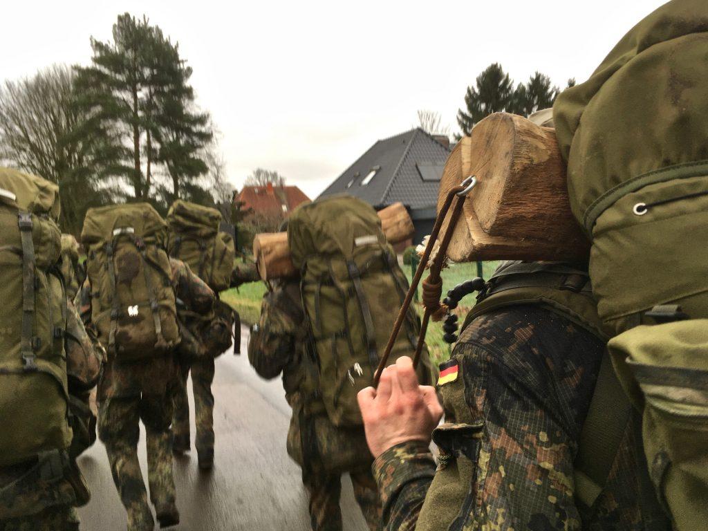 Soldaten im Feldanzug mit Rucksäcken, einige tragen zusätzlich Meterhölzer im Nacken