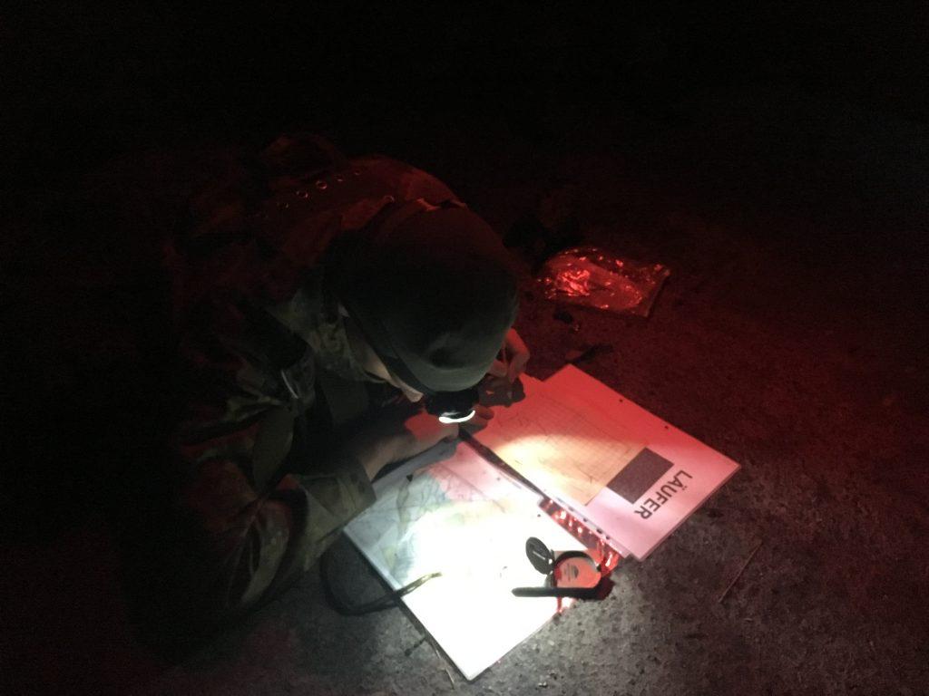 Soldat mit Karte und Kompass bei Dunkelheit im Schein seiner Kopflaterne