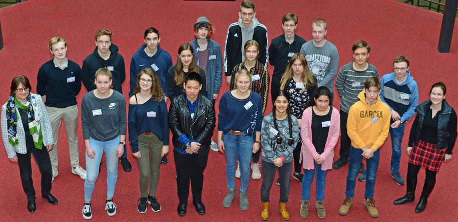 Eine Gruppe von 20 Jugendlichen und zwei Erwachsenen steht auf einem roten Teppich.