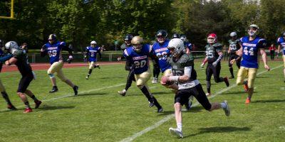 Ein Footballspieler mit dem Ball unterm Arm wird von vielen anderen verfolgt