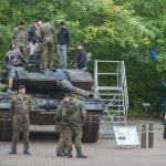 Soldaten stehen auf und vor einem Kampfpanzer