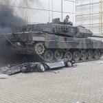 Ein Panzer hat ein Auto überfahren. Das Auto ist platt, der Panzer qualmt