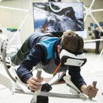 Ein Junge mit einer VR-Brille hängt in einem Gestell