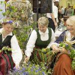 Frauen in bunten Trachten flechten Blumenkränze