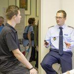 Ein Mann in Uniform spricht mit einem Jugendlichen.