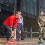 Eine Frau im Trainingsanzug wirft einen Volleyball von einer Bühne.