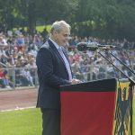 Ein Mann hinter einem Rednerpult, das in eine Bundesdienstflagge gehüllt ist.