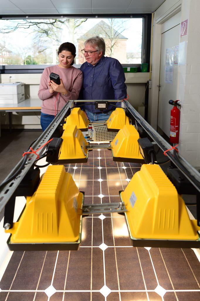 Eine Wissenschaftlerin und ein Wissenschaftler hinter einer Photovoltaikanlage