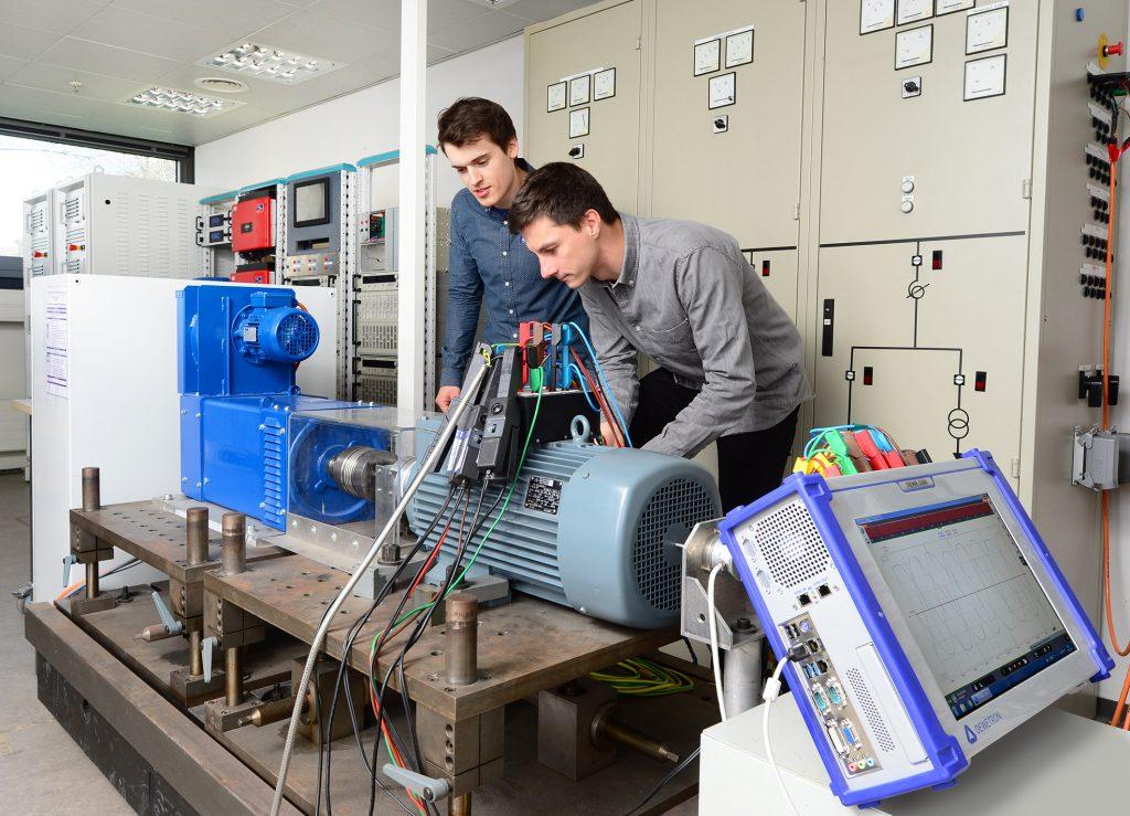 Zwei Wissenschaftler hinter einem Generator