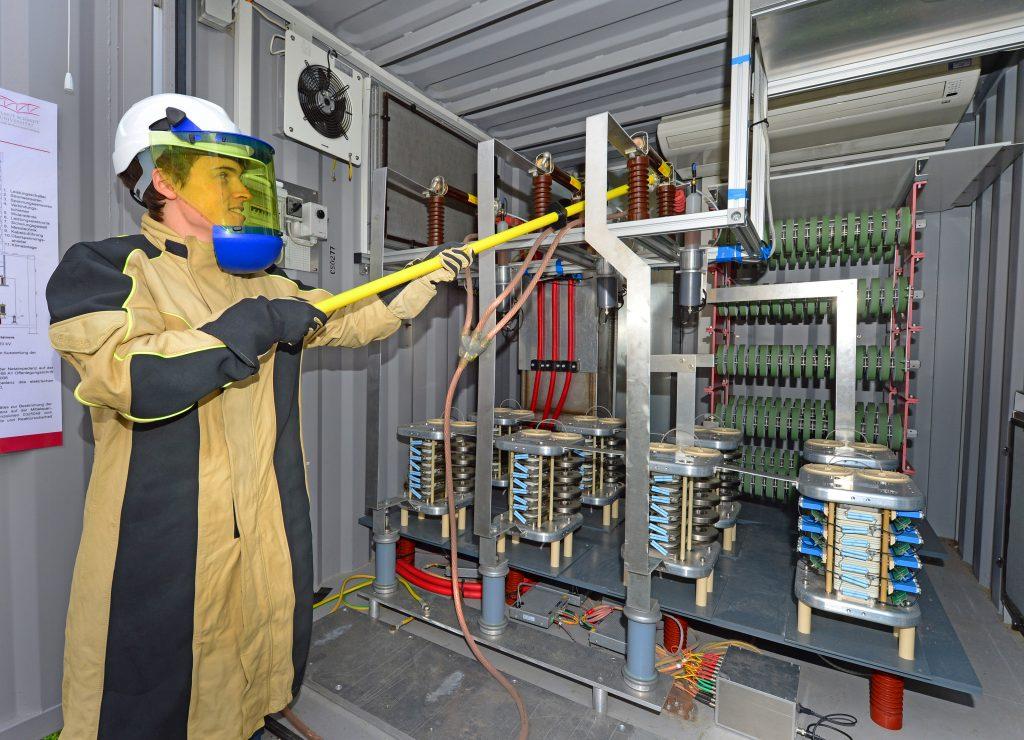 Ein Mann in einem Schutzanzug erdet eine elektrische Anlage