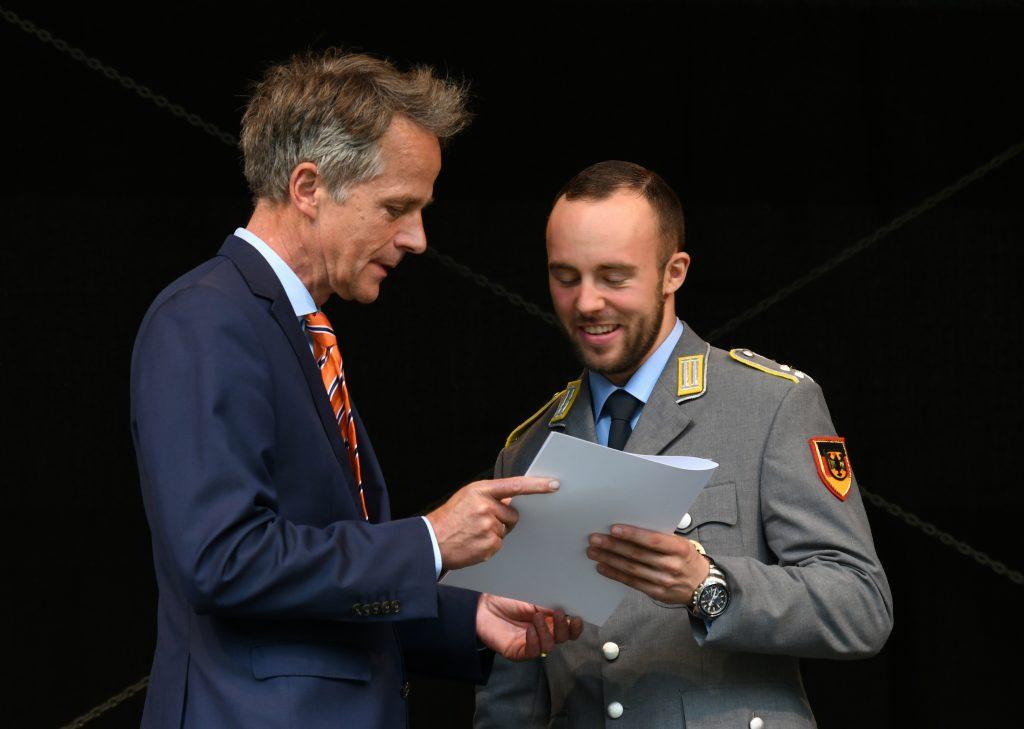 Ein Mann im blauen Anzug überreicht einem Soldaten in Heeresuniform eine Urkunde