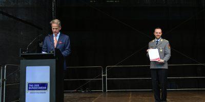 Ein Mann im blauen Anzug hinter einem Rednerpult, rechts davon ein Soldat in Heeresuniform mit einer Urkunde