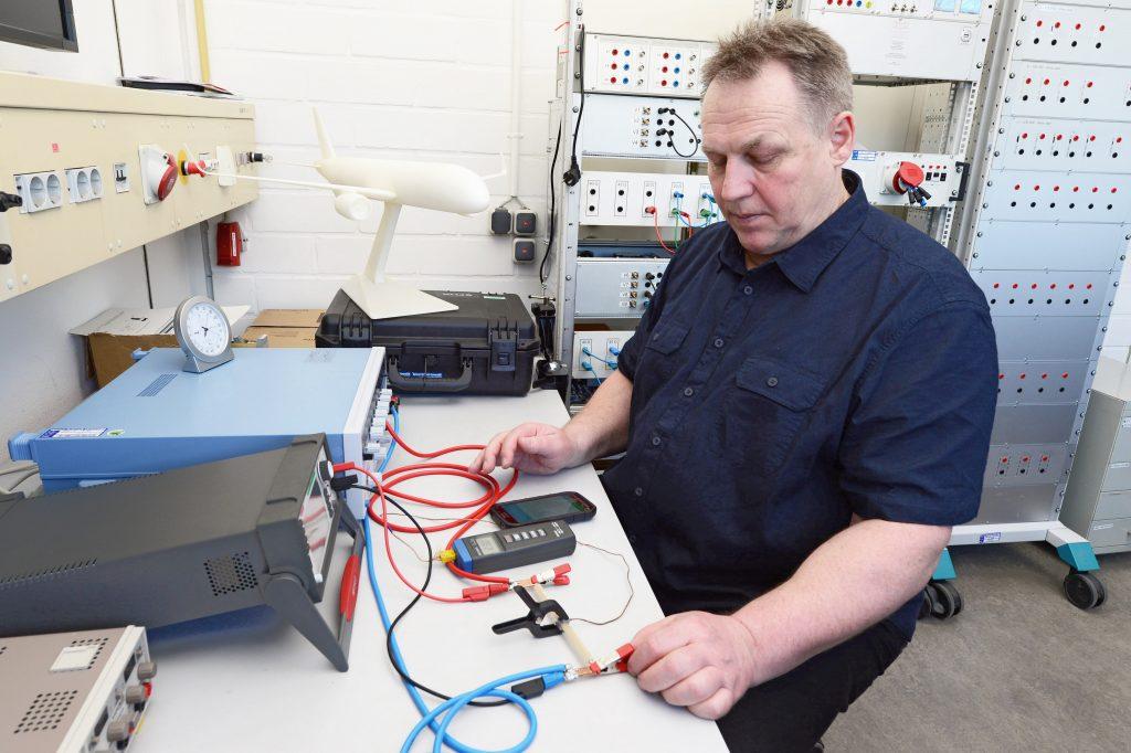 Ein Wissenschaftler misst ein elektrisches Bauteil