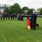 Ein Mann hinter einem Rednerpult steht vor eine Quarree aus angetretenen Soldaten