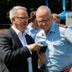 Ein Mann in einem Anzug zeigt einem anderen Mann in Generalsuniform etwas auf seinem Smartphone