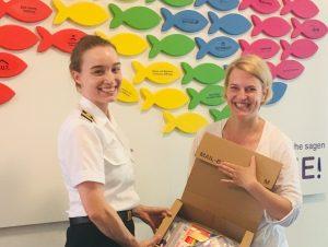 Eine Soldatin in der Uniform eines Kapitänleutnants der marine übergibt einen Karton an eine lachende Dame in Zivilkleidung