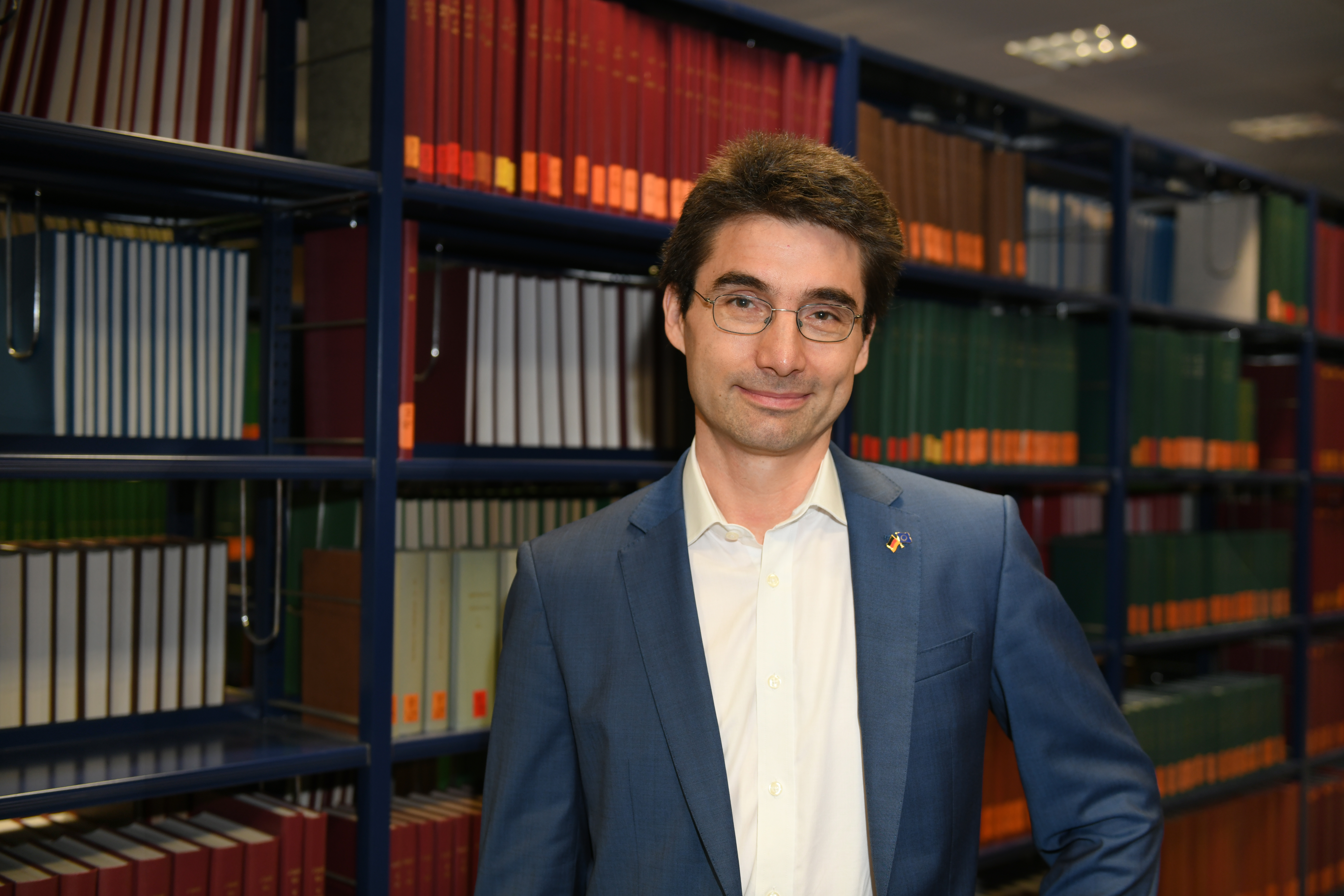 Ein Mann steht vor einem gut gefüllten Bücherregall. Er trägt einen offenen, grauen Anzug ohne Krawatte