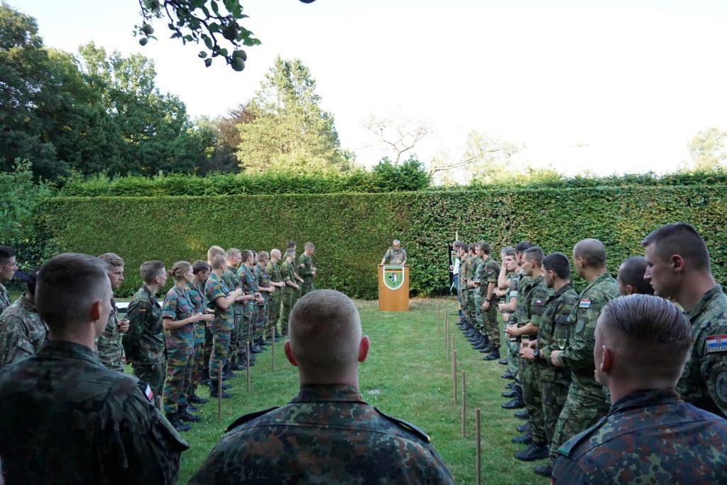 Es stehen viele Soldaten auf einer grünen Wiese, am Ende der Wiese steht ein Rednerpult mit einem Redner in Uniform