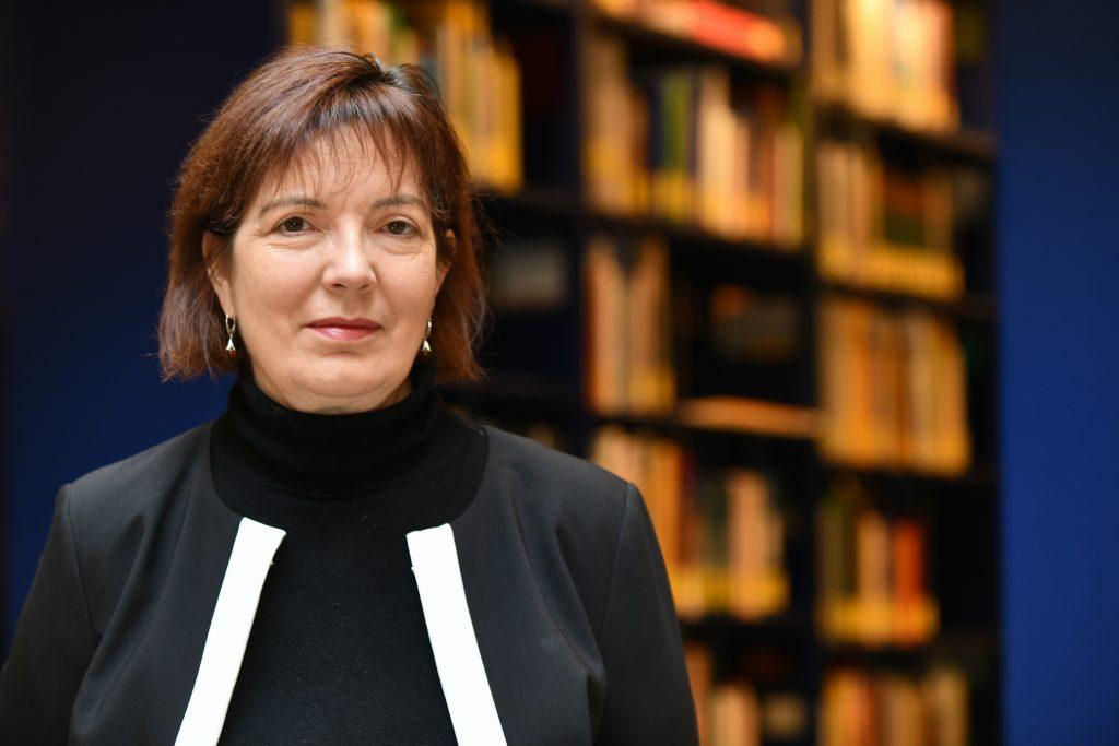 Eine Frau steht vor einem Bücherregal.