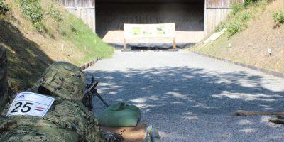 Ein Soldat liegt auf dem Boden und schießt mit einem Gewehr auf eine Zeilscheibe, dabei trägt er einen Helm. Auf dem Rücken hat er ein Schild mit einer Wettkampfnummer