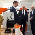 Drei Männer in einem Raum voller 3D-Drucker