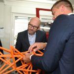 Drei Männer schauen auf eine orangefarbene Gitterstruktur, einer erläutert daran etwas.