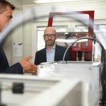 Ein Mann hinter einer Reihe von 3D-Druckern, daneben ein anderer Mann, der etwas erläutert.