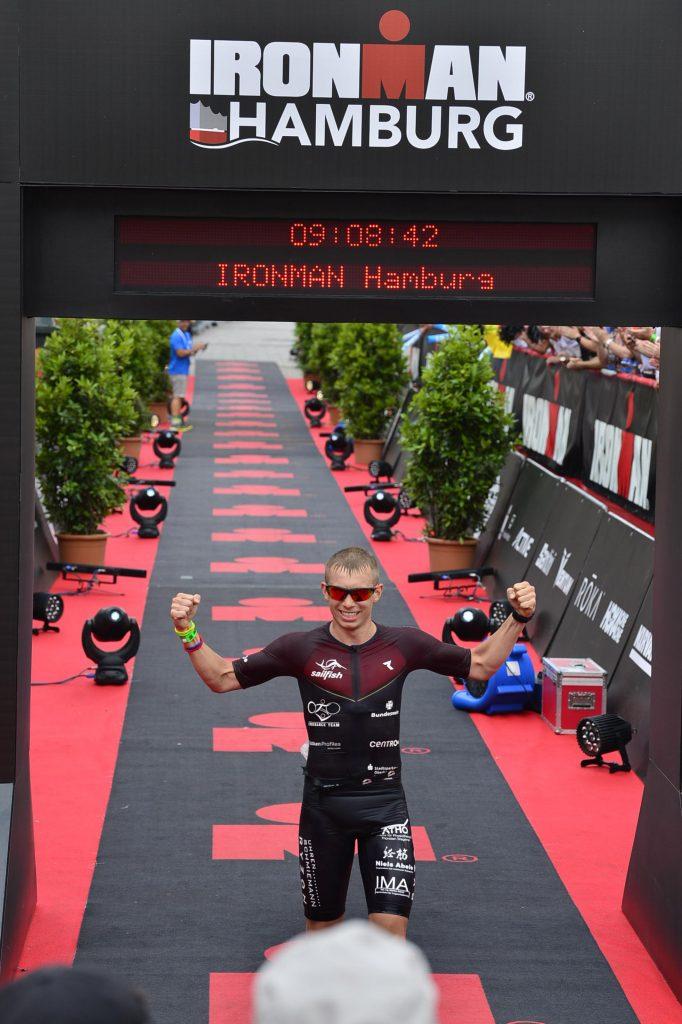 Ein Mann läuft mit Sonnenbrille durch den Zieleinlauf. Er hebt die Arme zum Jubeln.