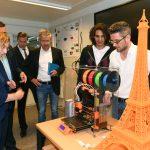Fünf Männer und eine Frau stehen um einen 3D-Drucker. Im Vordergrund ist ein bereits gedruckter Eiffelturm aus orangenem Kunststoff zu sehen.