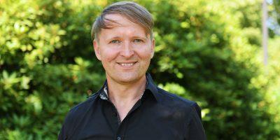 Portraitfoto eines Mannes in einem Schwarzen Hemd