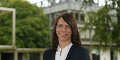 Eine Frau mit offenem Haar steht zwischen zwei Bücherregalen. sie trägt eine weiße Bluse und ein dunkles Jackett vor dem Universitätsgebäude. Sie lächelt.