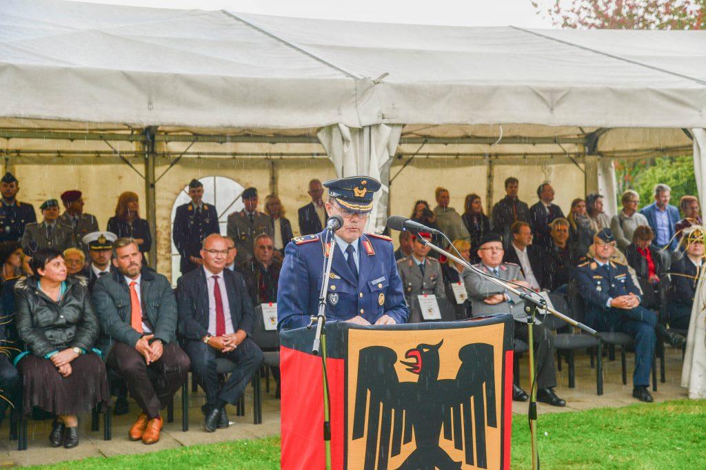 Ein Soldat steht an einem Rednerpult, im Hintergrund ist ein Zelt zu sehen, in dem viele Leute sitzen