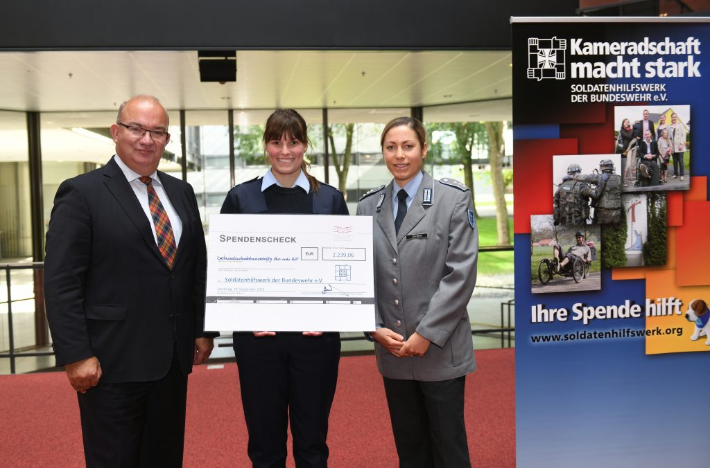 Ein Mann in einem dunklen Anzug mit karierter Krawatte und zwei Soldatinnen in Uniform, von denen eine einen übergroßen Barscheck über 2.239,06 Euro hält.