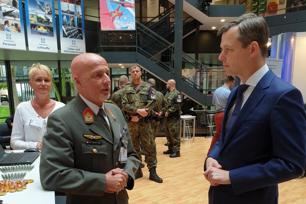 Ein junger mann im blauen Anzug unterhält sich mit einem Offizier in österreichischer Heeresuniform