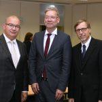 Drei Männer in dunklen Anzügen.