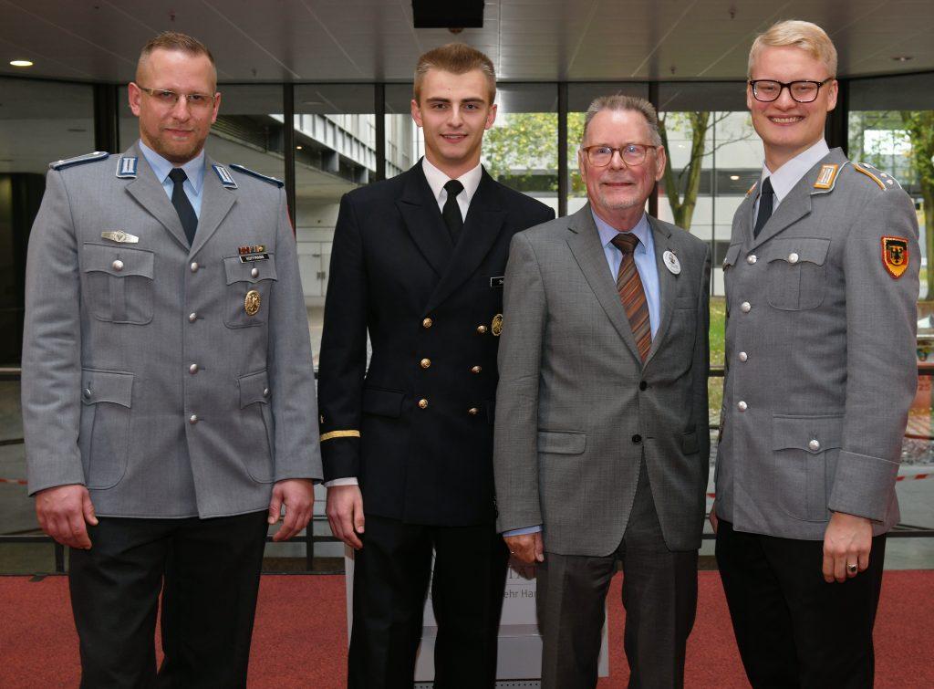 Drei Offiziere und ein Mann in einem grauen Anzug