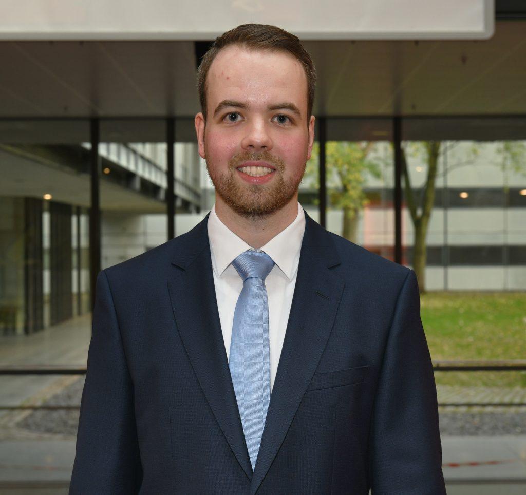 Ein junger Mann mit Bart in einem dunkelblauen Anzug mit hellblauer Krawatte