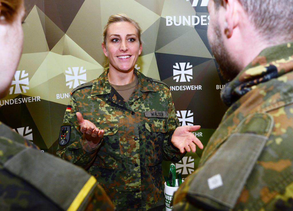 Eine Soldatin erklärt anderen Soldaten mit einer Geste etwas