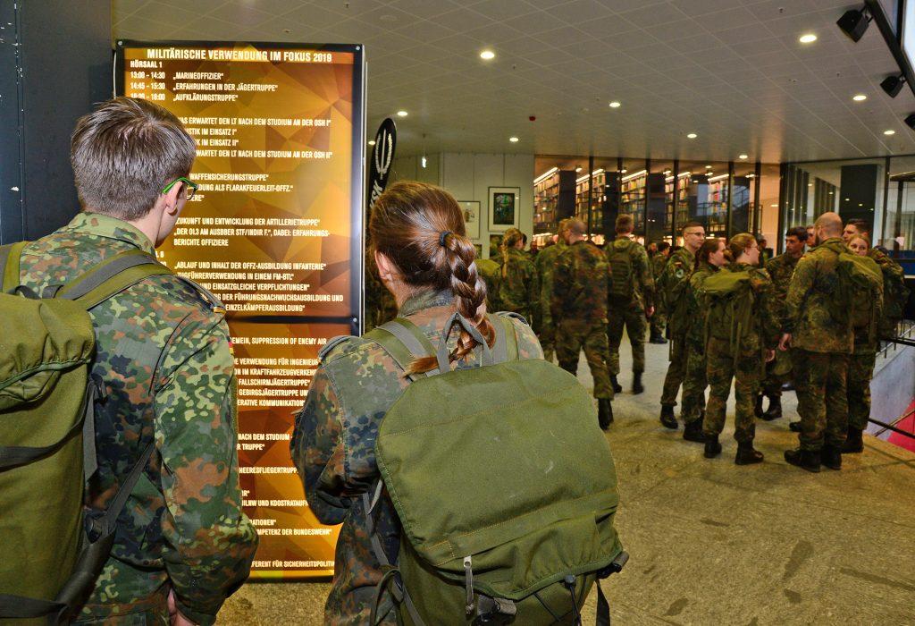 Zwei Soldaten stehen vor einer Informationswand