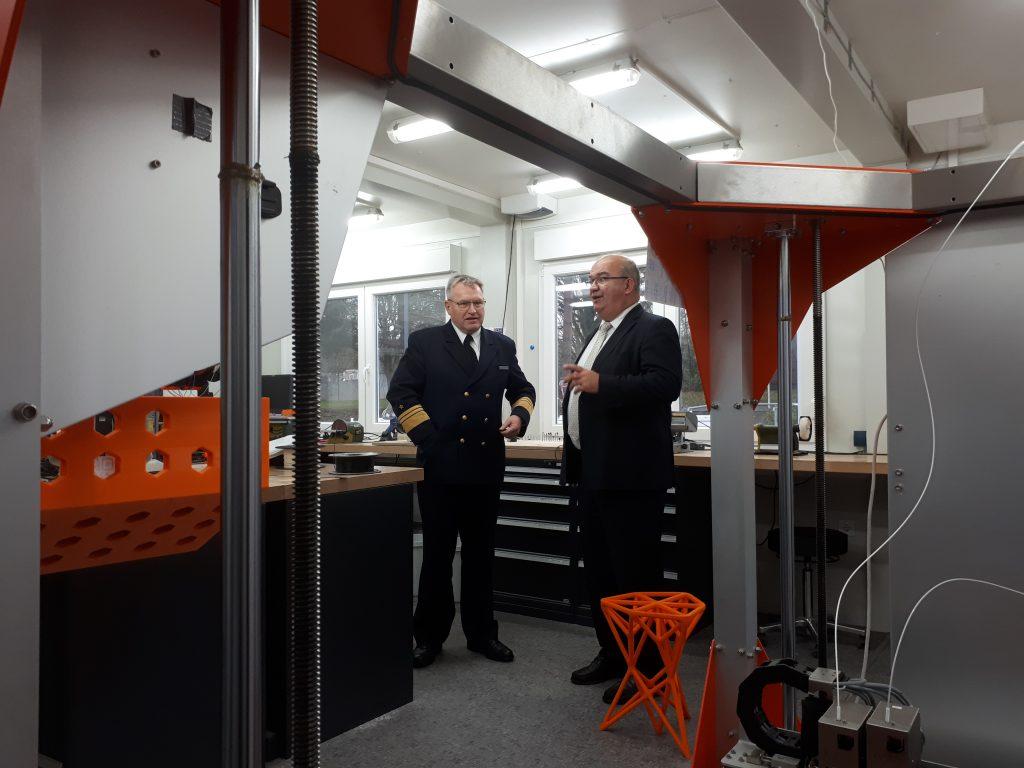 Zwei Herren stehen hinter einem 3D Drucker