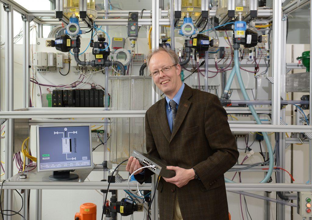 Ein Mann mit Sakko und Krawatte in einem Labor